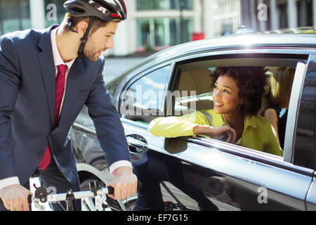 Businessman on bicycle talking to woman in car - Stock Photo