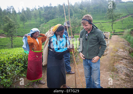 TOURIST TRYING ON TEA PICKING BASKET - Stock Photo