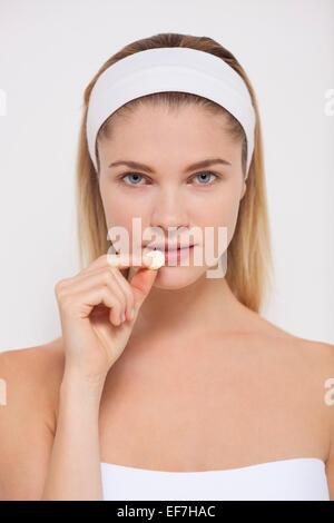 Beautiful woman taking pill - Stock Photo
