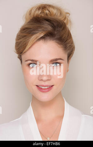 Portrait of a smiling woman in bathrobe - Stock Photo