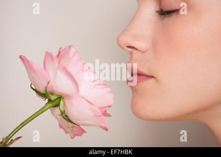 Beautiful woman smelling a flower - Stock Photo