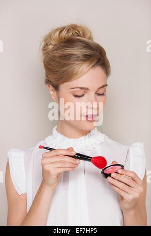 Beautiful woman holding make-up brush - Stock Photo