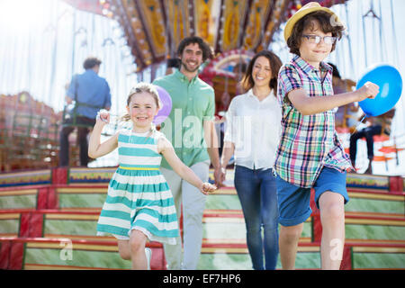 Children running in front of carousel, parents following them - Stock Photo