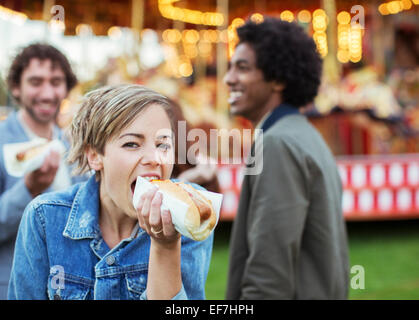 Three young people eating hot-dogs in amusement park - Stock Photo