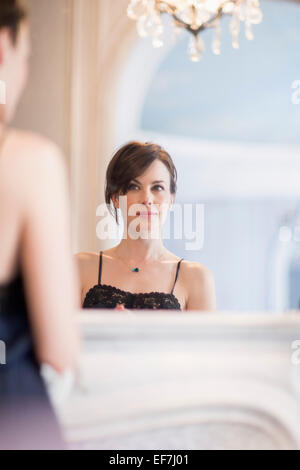 Reflection of a woman in mirror - Stock Photo