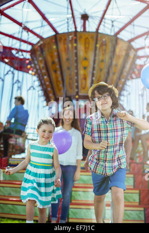 Children running in front of carousel, mother following them - Stock Photo