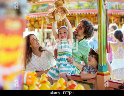 Girl holding teddy bear as trophy in fishing game in amusement park - Stock Photo