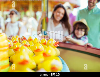 Boy trying to catch rubber duck on fishing game in amusement park - Stock Photo