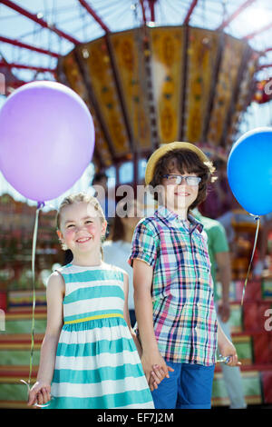 Portrait of boy and girl holding balloons in amusement park - Stock Photo