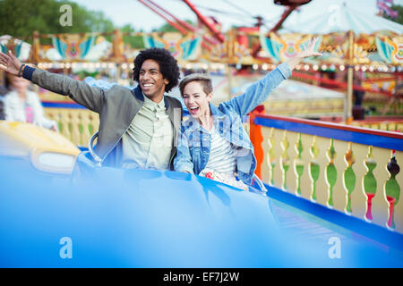 Cheerful couple on carousel in amusement park - Stock Photo