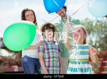 Young girl holding bunch of balloons, family standing behind her - Stock Photo