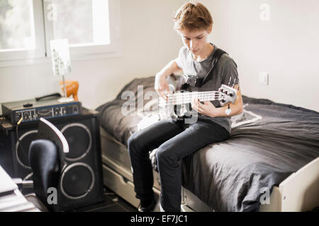 Teenage boy playing a guitar on bed - Stock Photo