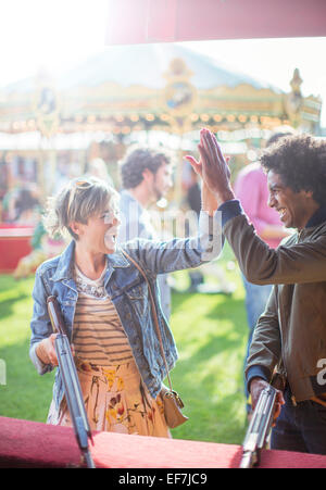 Young couple giving high five in amusement park - Stock Photo