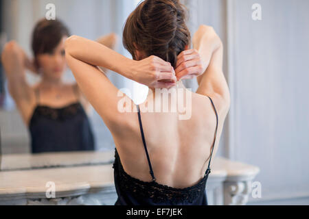 Woman putting on necklace in front of mirror - Stock Photo