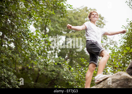 Teenage boy playing in a park - Stock Photo