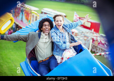 Cheerful couple having fun on carousel in amusement park - Stock Photo