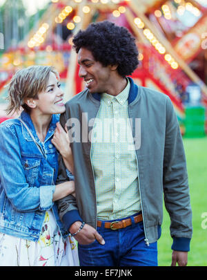 Young multiracial couple smiling to each other in amusement park - Stock Photo