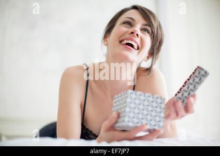 Beautiful happy woman holding a gift box - Stock Photo