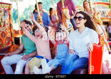 Family on carousel in amusement park