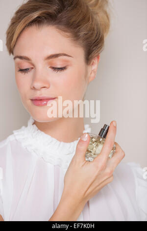 Beautiful woman applying perfume - Stock Photo