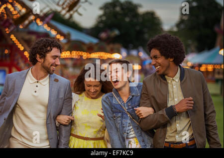 Two couples walking in amusement park and laughing at dusk - Stock Photo