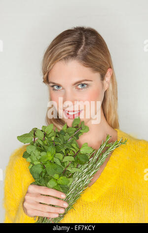 Portrait of a beautiful woman holding herbal leaves - Stock Photo