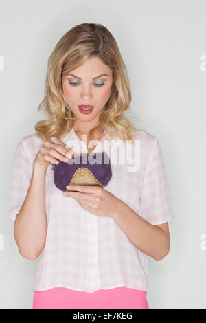 Surprised woman looking her purse - Stock Photo