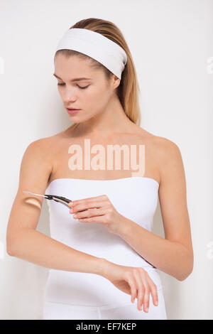 Beautiful woman examining her skin with magnifying glass - Stock Photo
