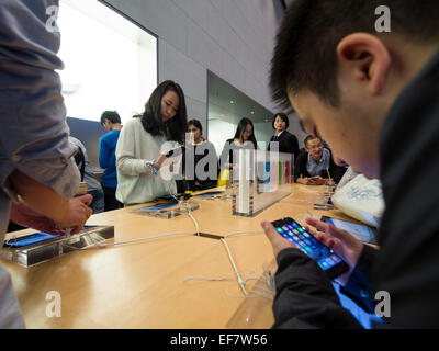 Costumers browsing Apple products at the Apple store located on Nanjing Road in Shanghai, China - Stock Photo