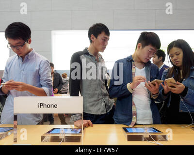 Costumers trying out Apple iPhones at the Apple store located on Nanjing Road in Shanghai, China - Stock Photo