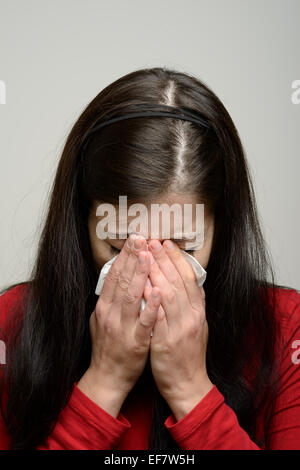 Woman crying and wiping her tears with a paper tissue