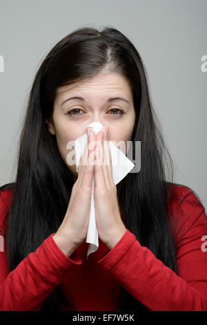 Young woman in red blouse blowing her nose with tissue paper - Stock Photo