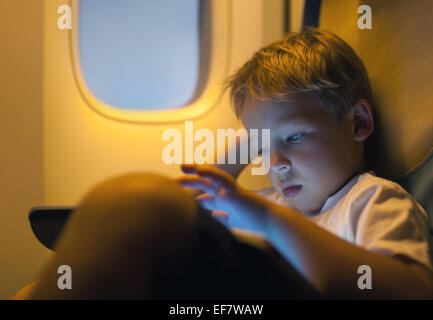 Little boy using tablet computer during flight - Stock Photo