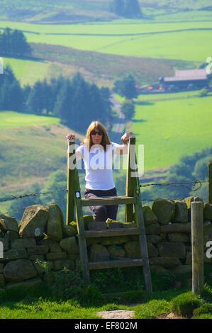 Woman climbing a style on Hadrian's Wall Path Walton Northumberland England UK - Stock Photo