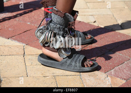 Young street performer outside a cafe in South Africa using recycled can tops to add effect when dancing - Stock Photo