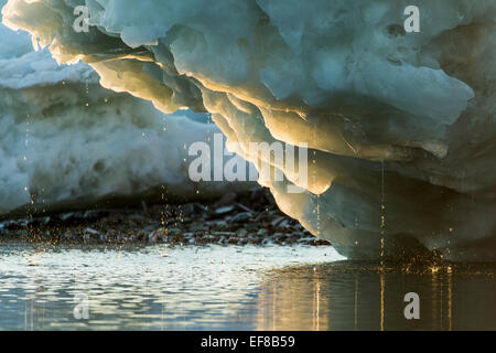 Canada, Nunavut Territory, Water drips from melting iceberg along Frozen Channel at northern edge of Hudson Bay - Stock Photo
