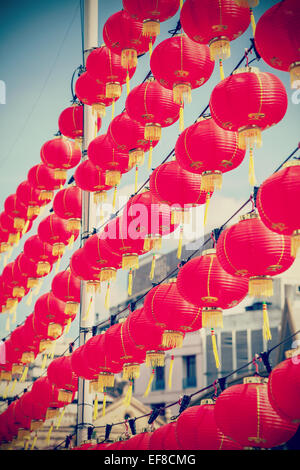 Retro filtered Chinese red paper lanterns against blue sky. - Stock Photo