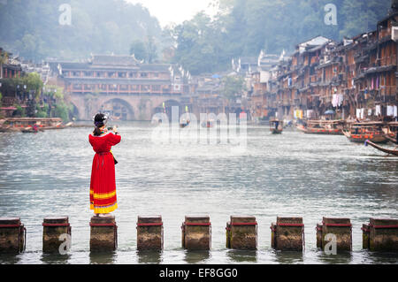 Tourist in traditional Miao costume takes a picture on the Tuojiang River, Fenghuang, China - Stock Photo