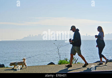 man and pregnant wife walk the dog on the waterfront in Sausalito - Stock Photo