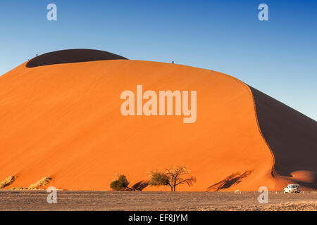 Five tourists walk on the top of giant orange Dune 45 in Sossusvlei, Namib Desert, Namibia, Africa - Stock Photo