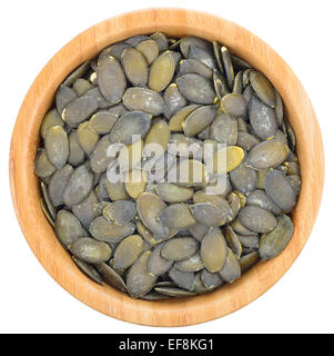 Shelled pumpkin seeds in a wooden bowl isolated od white background. Top view. - Stock Photo