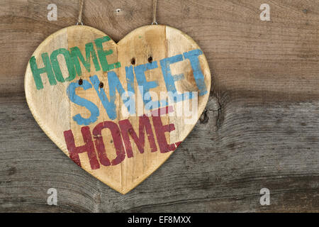 'Home Sweet Home' message wooden heart sign from recycled old palette on rough grey wooden background, copy space - Stock Photo