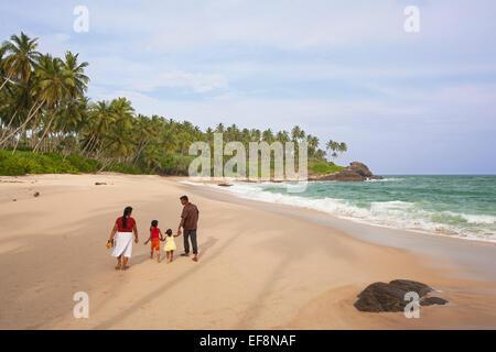 SRI LANKAN FAMILY TAKING WALK ALONG GOYAMBOKKA BEACH NEAR TANGALLA - Stock Photo