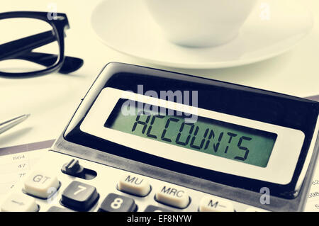 the word accounts written in the display of a calculator on an office desk, with a cup of coffee or tea in the background - Stock Photo