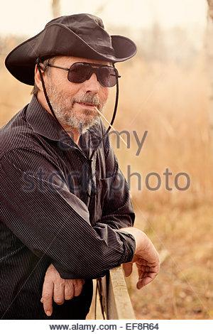 Portrait of senior man wearing sunglasses and cowboy hat - Stock Photo