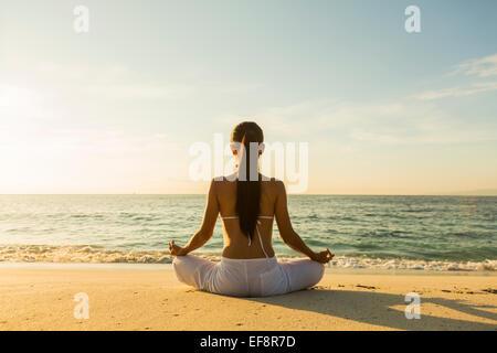 Woman meditating on beach - Stock Photo