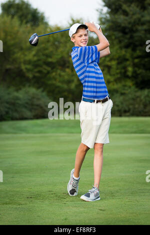 Teenage boy playing golf - Stock Photo