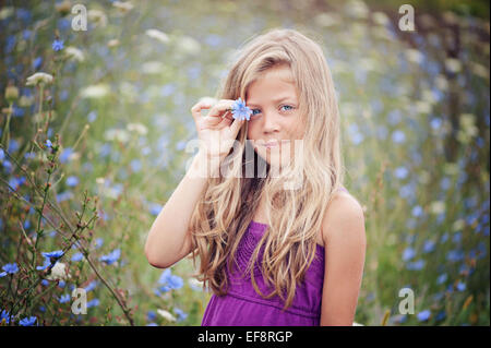 Portrait of young girl standing in chicory field holding a flower