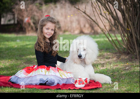 Portrait of girl (6-7) and white poodle on picnic blanket - Stock Photo