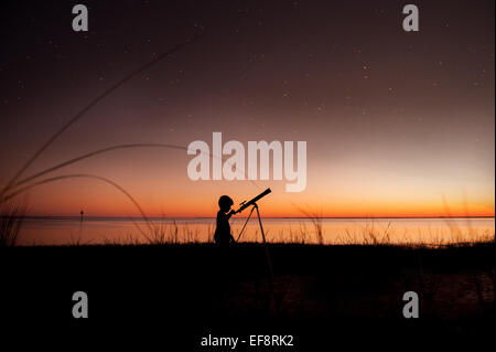 Silhouette of boy looking at stars through telescope - Stock Photo